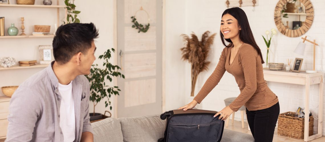 Vacation Concept. Joyful Travelers Couple Packing Suitcase For Vacation At Home. Selective Focus